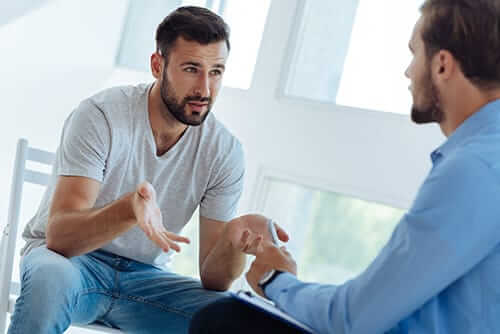 Client and counselor discussing a Costa Mesa cocaine addiction treatment program for him